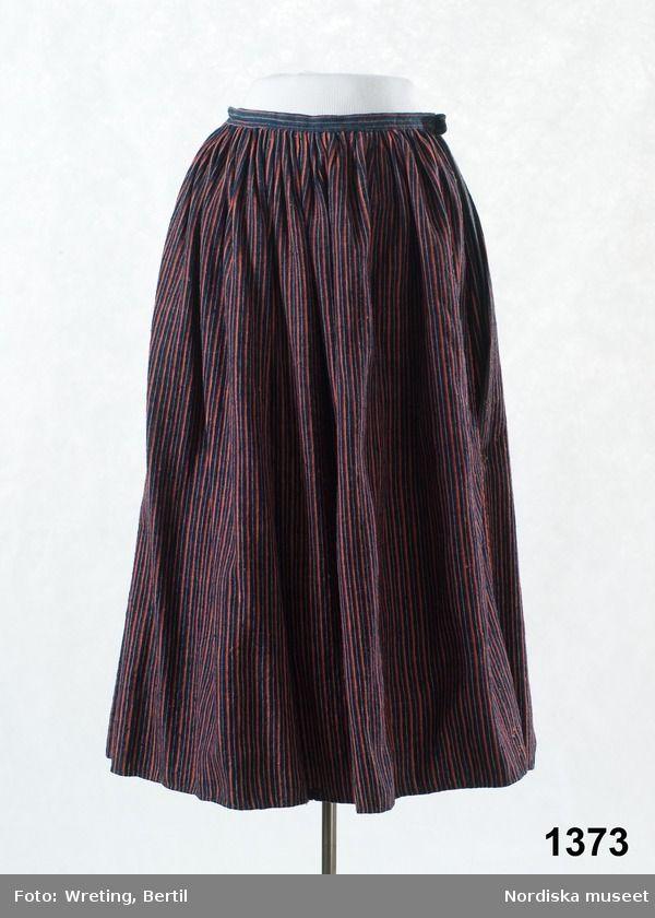 Kjol av halvylle vävd i tuskaft, varp av vitt lingarn, inslag av entrådigt ullgarn, smalrandig i blått, rött och rosa, samma tyg som i tillhörande tröja 1372. Sydd av en hel våd, tätt veckad upptill, mot 2,5 cm bred midjelinning av ett liknande blå-och rödrandigt tyg, sprund i sömmen som är på vänster sida. I nederkanten enkel smal fåll, ingen skoning.  Stoppad på flera ställen med tjockt brunt ullgarn. Smärre malskador. Handsydd med oblekt lintråd. /Berit Eldvik 2011-06-28