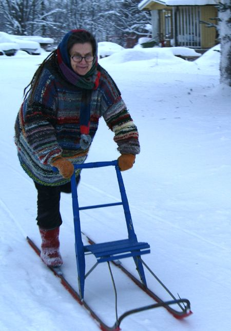 The kicksled consists of a chair mounted on a pair of flexible metal runners which extend backward to about twice the chair's length. The sled is propelled by kicking the ground by foot. There is a handlebar attached to the top of the chair back. Kicksled is POTKUKELKKA in Finnish.