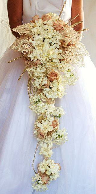 Flaunt it Fabulously bouquet was inspired by the fashion of the era. The use of lace, pearls, beads, and feathers was prominent in the fashionable upper layers of society. If you had it you flaunted it! It was all about opulence and luxury. Gardenias, Stephanotis, Quicksand Roses, Lace and Colored Pearls and Jewels.  Cindy Anderson, AIFD, PFCI. http://www.aboutflowersblog.com/flaunt-it-fabulously/