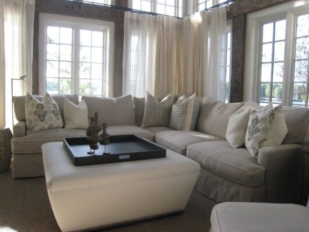 eye catching white ottoman on center with tray as coffee table surrounded by light grey skirted