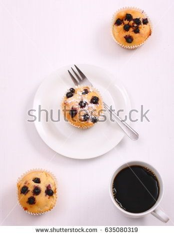 Delicious muffins with blueberries and cup of black coffee on white table.