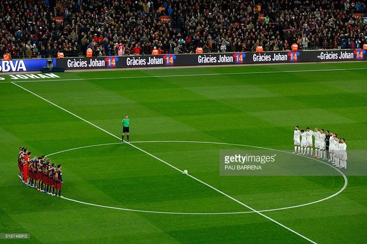 Real Madrid's and FC Barcelona teammates stand for a moment of silence for the deceased former Dutch football player Johan Cruyff who died on March 24, before the 'clasico' Spanish league football match FC Barcelona vs Real Madrid CF at the Camp Nou stadium in Barcelona on April 2, 2016. / AFP / PAU BARRENA