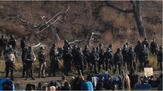 A situation is unfolding as you read this. A live feed with currently 60k people watching, 56k comments and 80k shares (and growing) is being shown on Facebook. Kevin Gilbert seems to be the only LIVE feed coming from Standing Rock at a police blockade on a bridge on HWY 1806. They are using extreme force on unarmed, peaceful water protectors.