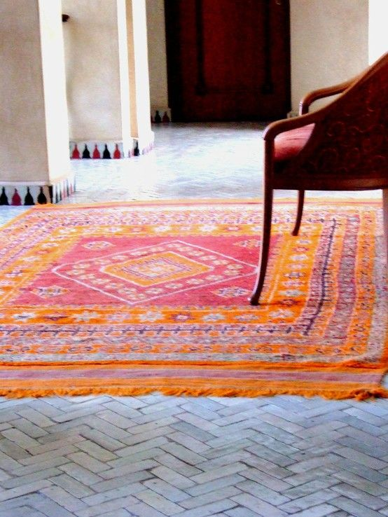 tile laid in a herringbone pattern with a colorful antique rug on top....this is ME!