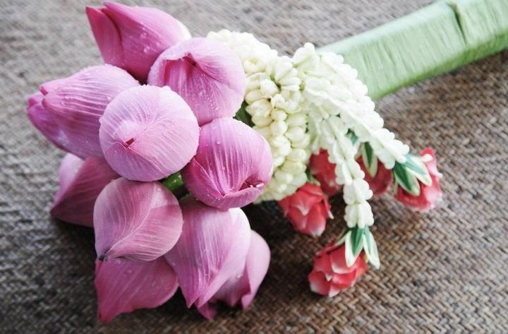 A fresh lotus bouquet with jasmine garlands is perfect for a Thai beach wedding. At Four Seasons Resort Koh Samui, Thailand.
