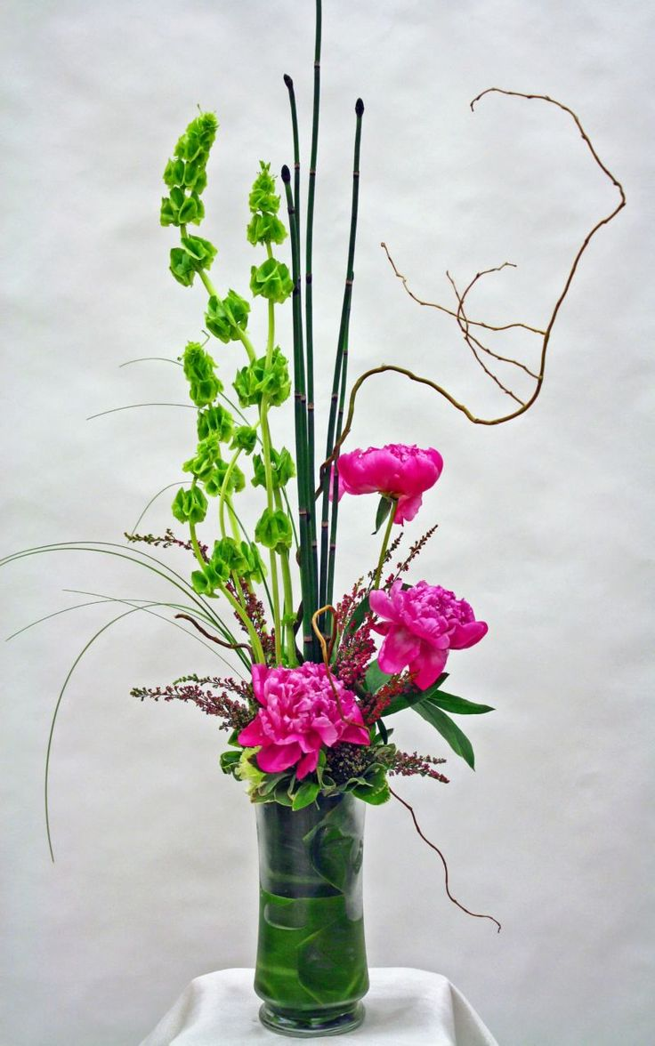 Tall Modern Floral Arrangement with Pink Peonies, Bells of Ireland, Curly Willow, Horsetail, and Ti Leaves.