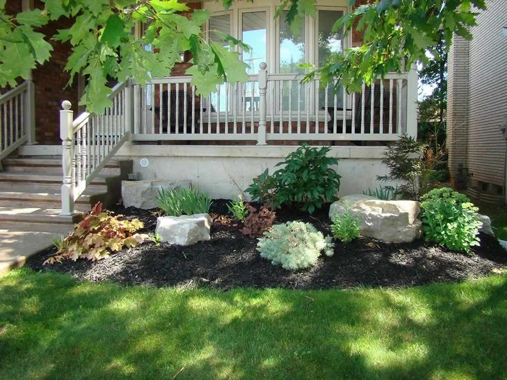 beautiful small garden with armour stone  shrubs  and black mulch