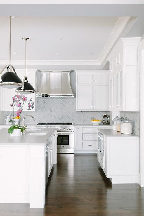 A polished steel French hood is mounted to gray marble herringbone backsplash between stacked white cabinets above a stainless steel dual range flanked by white lower cabinets topped with a honed carrera marble countertop.