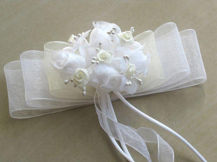 Lazo de comunión o ceremonia en tonos blanco y blanco roto, adornado con flores, lleva una peineta transparente como sujección al cab...