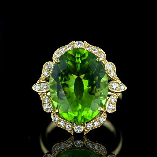 Gorgeous Peridot and Diamond Ring. A bright and lively faceted oval Peridot is enthroned in a lovely, feminine 18 karat yellow gold and diamond setting with Edwardian era influences. An extravagant and regal fun ring.
