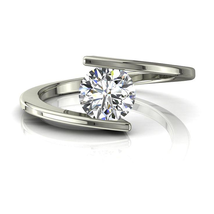 Solitaire bague diamant de fiançailles 1 carat or blanc Arabella  Diamants et Carats vous propose Arabella, une bague solitaire diamant à la ligne très épurées et haute joaillerie. Sertie et enlacée par la monture, la pierre centrale est un diamant rond de la forme brillant de 1 carat.  Fabriquée dans nos ateliers, cette bague de fiançailles se décline en or jaune, blanc,ou rose de qualité 18 carats.  - Couleur : I-H-G-F-E-D - Pureté : SI-VS-VVS - Poids diamant central : 1 carat - Diamètre…