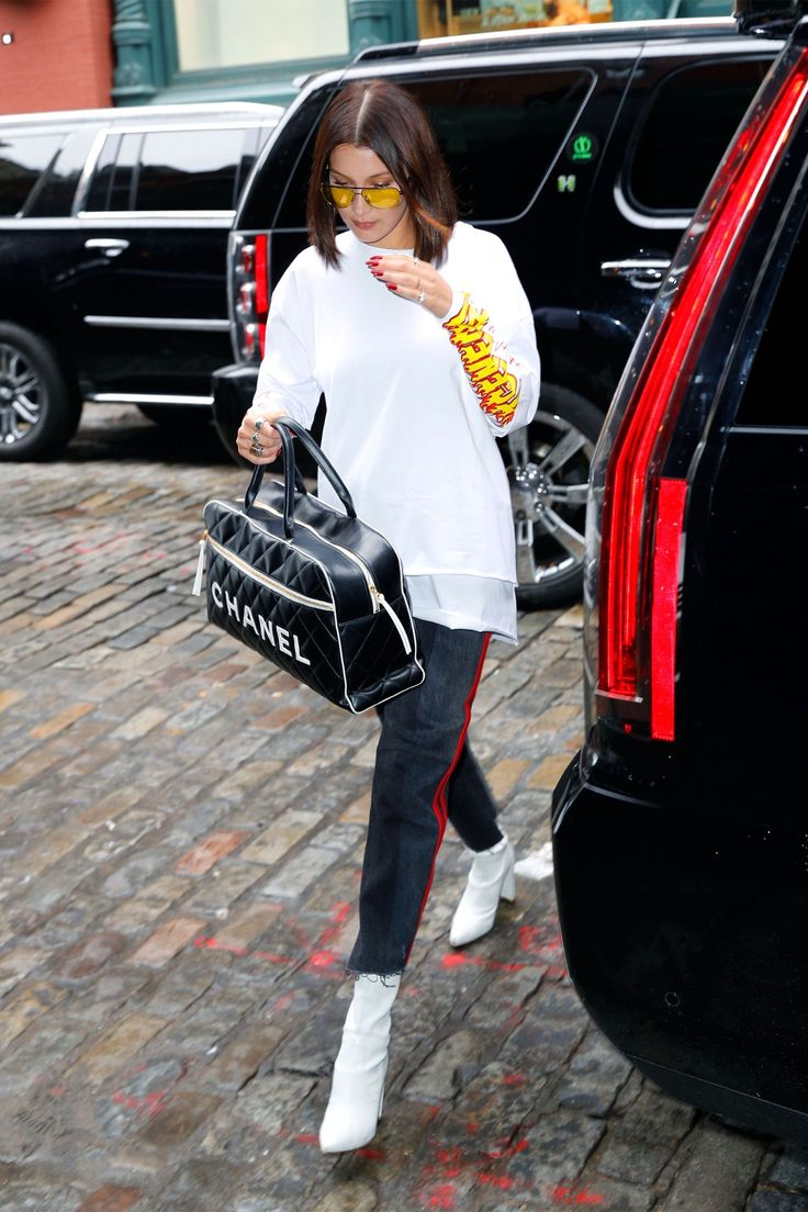 Bella Hadid in a white graphic tee with red leather striped Vetements jeans, Stuart Weitzman ankle boots, a Chanel duffel bag and yellow tinted aviator sunglasses while out in New York City