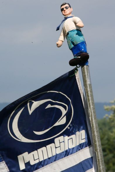 PENN STATE – PATERNO – A doll depicting former Penn State football coach Joe Paterno adorns the top of a Penn State flag pole of fans tailgating outside the stadium before an NCAA football game between Penn State and Massachusetts on Saturday, Sept. 20, 2014, in State College, Pa. (AP Photo/Keith Srakocic)