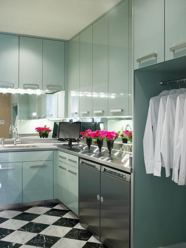 Lacquered blue cabinets and a mirrored backsplash make this an elegant spot to do laundry. This hue is subtle enough to fill a whole room without being too overpowering. Design by Jamie Herzlinger