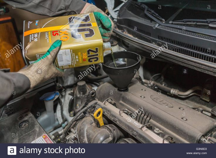 Download this stock image: Changing the oil in the garage, Moscow, Russia - G3N9D3 from Alamy's library of millions of high resolution stock photos, illustrations and vectors.