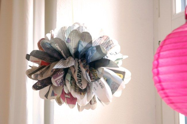 newspaper pompom hanging in window