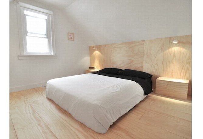 Daniel and Valerie of Hindsvik Shop created this plywood headboard in their bedroom, which runs the length of the wall with two plywood block tables on either side.
