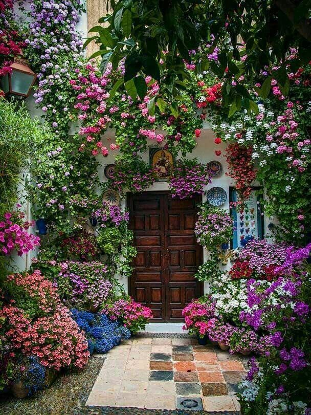 What a grand entrance! A doorway totally surrounded by a variety of different colored flowers. What a welcome for any guest! What a sight to enjoy for any homeowner!