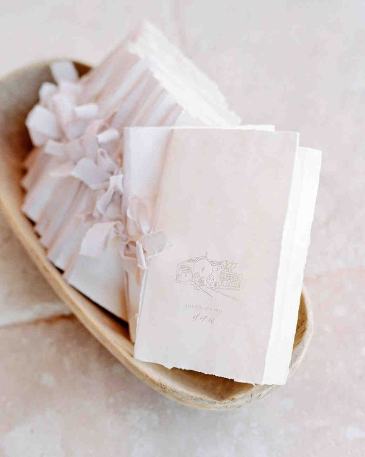 A Malibu Wedding With a Surprise Reception Location | Martha Stewart Weddings - Ceremony programs featured a custom illustration of the Mission San Fernando Rey de España, sketched by Kelsey Malie. They were printed on handmade Arpa paper and tied with rose quartz-colored silk ribbons from FrouFrou Chic.
