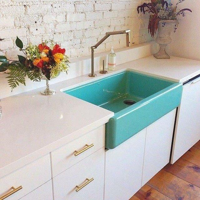 White countertops, white cabinets, gold pulls, gold faucet and pop of color farm sink.  Aqua teal kitchen sink