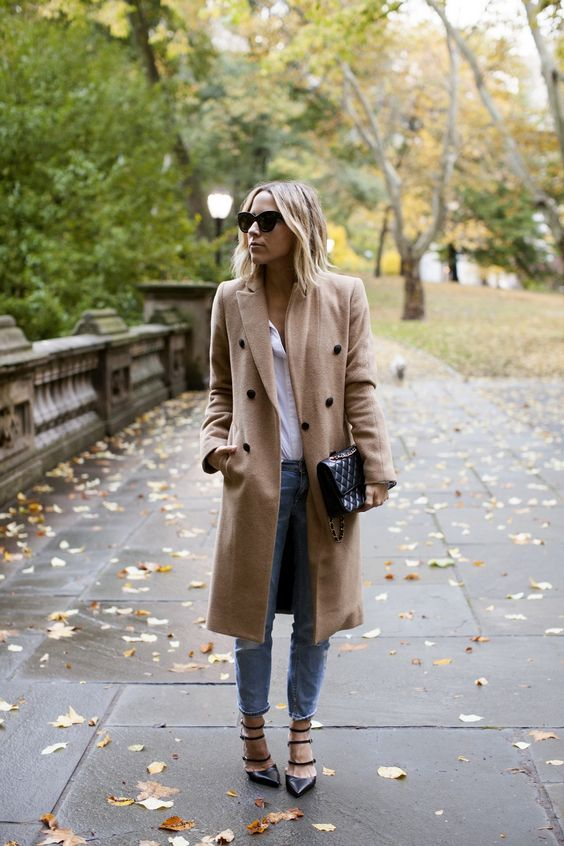 Camel coats are the must have this fall; Jacey Duprie wears hers with a white blouse, jeans, and strappy heeled sandals.