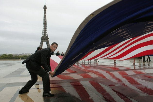 An American flag is unfurled during a commemoration to mark the 10th anniversary of the Sept. 11 attacks on the United States, at the Trocadero plaza , near the Eiffel tower, seen in the background, in Paris, Sunday, Sept. 11, 2011. (AP Photo/Thibault Camus)...