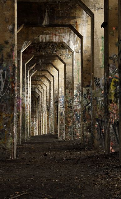 Underside of elevated train tracks on a pier in the Delaware River in the Port Richmond area of Philadelphia.  The curving maze of concrete support pillars has been converted into an excellent paintball battleground