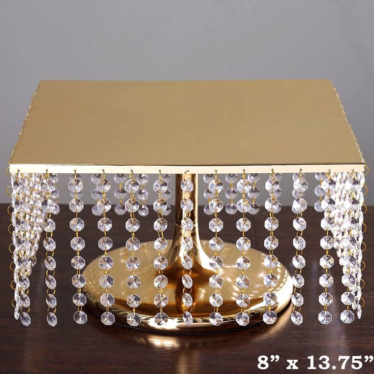 """14"""" Bejeweled Gold Square Crystal Pendants Metal Chandelier Wedding Riser Cake Stand   Create a breathtakingly glitzy display of your precious Wedding Cake with this deluxe bejeweled chandelier crystal cake stand. Add oodles of shimmer and glimmer to your cake or dessert tables with our plush crystal accented metallic chandelier cake display stands that will mesmerize the beholders with their modish square shape and glistening gold luster."""