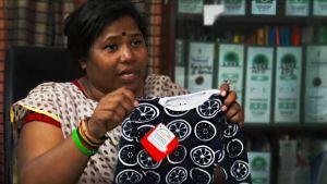 Bangladeshilaisen ammattiyhdistysjärjestön toiminnanjohtaja Kalpona Akter ja Reiman vauvanpaita.