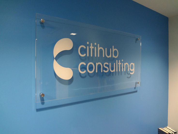 Custom clear acrylic / clear plexiglass panel with flat die-cut digital graphic logo in opaque white, mounted with 4 corner polished stainless steel standoffs onto interior painted blue drywall in NYC. For more information on office signs, visit http://www.SignsVisual.com