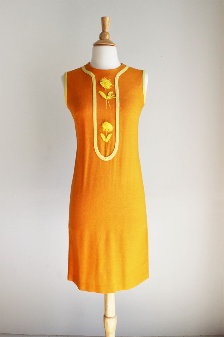 This is the most charming and perfect little dress for late Summer transitioning into Autumn. Orange barkcloth 60's mod dress with yellow trim and the cutest floss flowers on the front. To me they loo