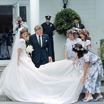 Caroline Bouvier Kennedy, in her wedding dress scattered with shamrocks and designed for her by Carolina Herrera, stands with her uncle Senator Ted Kennedy outside Our Lady of Victory Catholic Church in Centerville, Massachusetts, on July 19, 1986. The bride's cousin, Maria Shriver, was matron of honor and wore a lavender print dress.