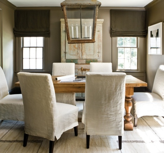 beautiful elements in this dining room - linen slip covered chairs, rough table and oversized lantern - lovely!