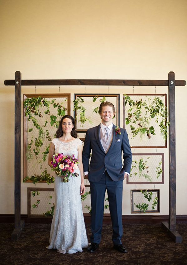 Jill Hoemann of City Blossoms filled old picture frames with hops, pepper berries, similax, and berry branches to create this beautiful botanical backdrop. | Photo by Rapp Photography