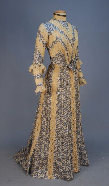 PRINTED SILK HIGH NECK GOWN,   c. 1902.   2-piece with blue and white abstract printed and tucked silk panels with bands of scrolling floral cream lace, boned long sleeve bodice with ruffle at elbow, slightly trained skirt, lined in cream silk with hem ruffle. B-36, W-25, skirt front L-41, back L-47.