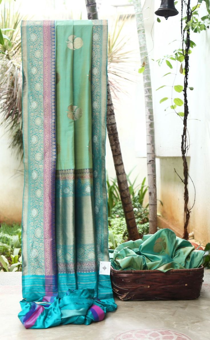 SPLENDID TURQUOISE GREEN IRIDESCENT GOLDEN YELLOW BENERES SILK WITH GOLDEN AND SILVER FLORAL ZARI BUTTAS ALL OVER HAS RADIANT GOLD ZARI ON TURQUOISE GREEN, DARK PINK, ROYAL BLUE BORDER AND PALLU TH...