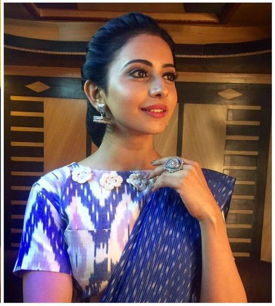Rakul Preet gives a fresh and unconventional twist to a saree as she attends the Pro Kabaddi event. She was all decked up in a blue ikat saree by Preetham Jukalker. She carried off the look with immense grace and poise. She teamed the saree with a white and blue ikat blouse which features pocket …