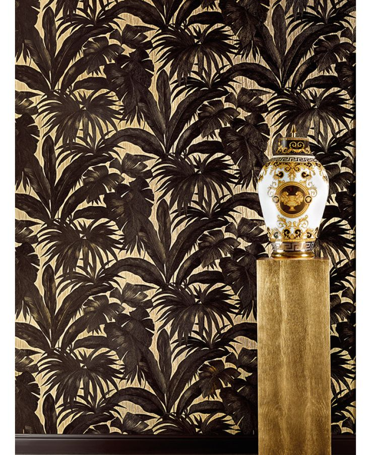 The Versace Giungla Palm Leaves Wallpaper features an exquisite black Versace palm leaf design on a soft gold backdrop. Free UK delivery available