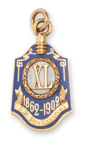 """The Machine-Building Factory """"Ludvig Nobel"""": A Fabergé gold and enamel commemorative badge, St. Petersburg, 1902, commemorating the 40th anniversary of the factory's founding in 1862, one side centered with the Roman numerals XL within a gold wreath on a blue ground, set above a ribbon engraved in Cyrillic G.T. Fredrikson, the reverse with gold machine building tools surmounted by the Imperial eagle on a white ground."""