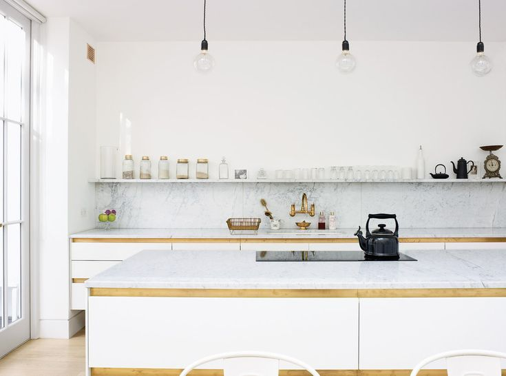 white marble countertop, backsplash and shelving. exposed filament industrial lighting but glamorous metal brass cabinet pull details, brass faucet, blonde wood floors and white walls. designed by Harriet Anstruther