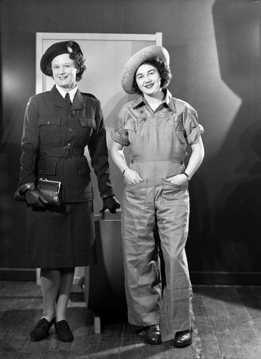 Unidentified models wearing Women's Land Service uniforms, circa 1942. One wears a suit, the other is dressed in overalls. Photograph taken by Gordon Burt.