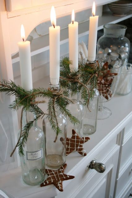 clear glass bottles, green spruce branches, hemp tie and white candles. sweet and simple.
