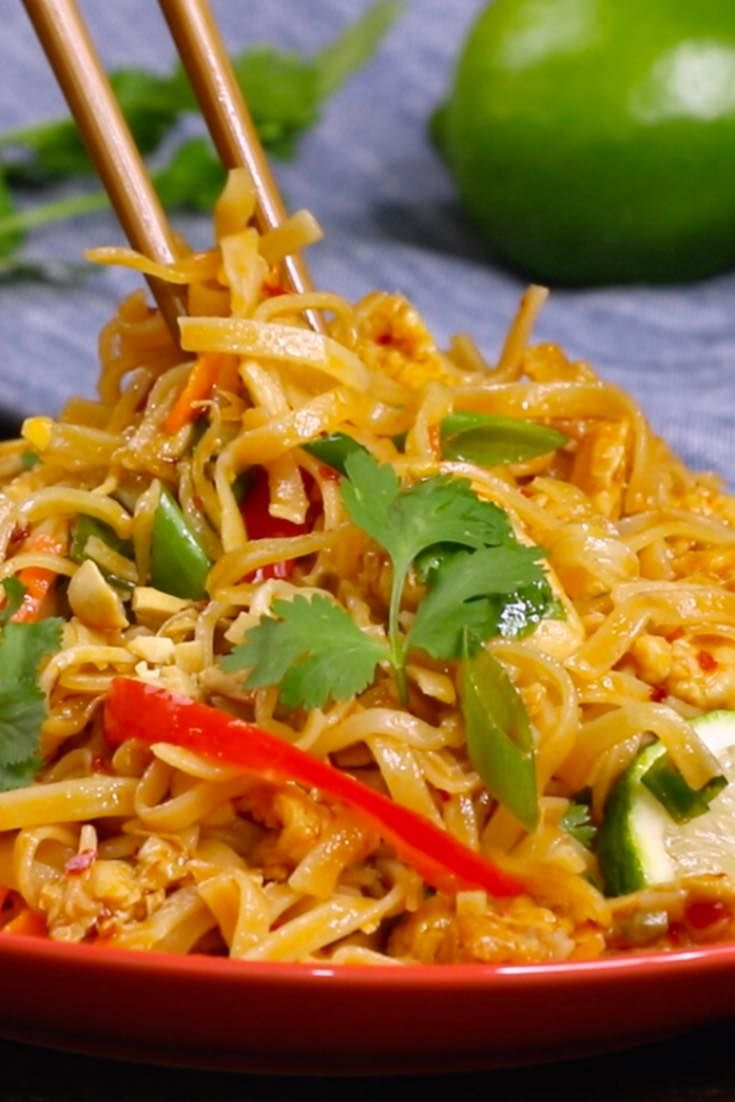 This is a closeup photo of chopsticks picking up homemade Chicken Pad Thai from a serving plate with lime and cilantro garnish
