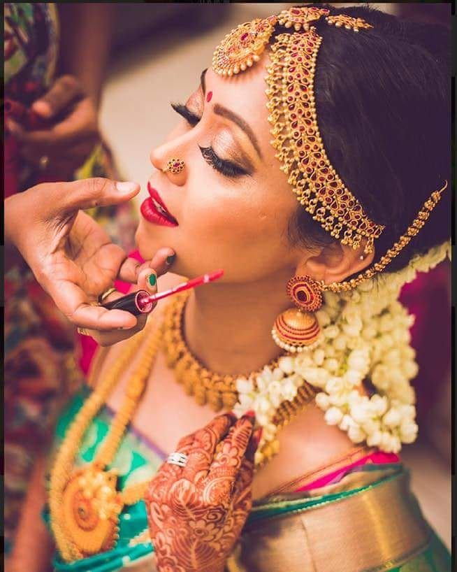 South Indian bride. Gold Indian bridal jewelry.Temple jewelry. Jhumkis. Green and pink silk kanchipuram sari. Braid with fresh jasmine flowers. Tamil bride. Telugu bride. Kannada bride. Hindu bride. Malayalee bride.Kerala bride.South Indian wedding. Pinterest: @deepa8