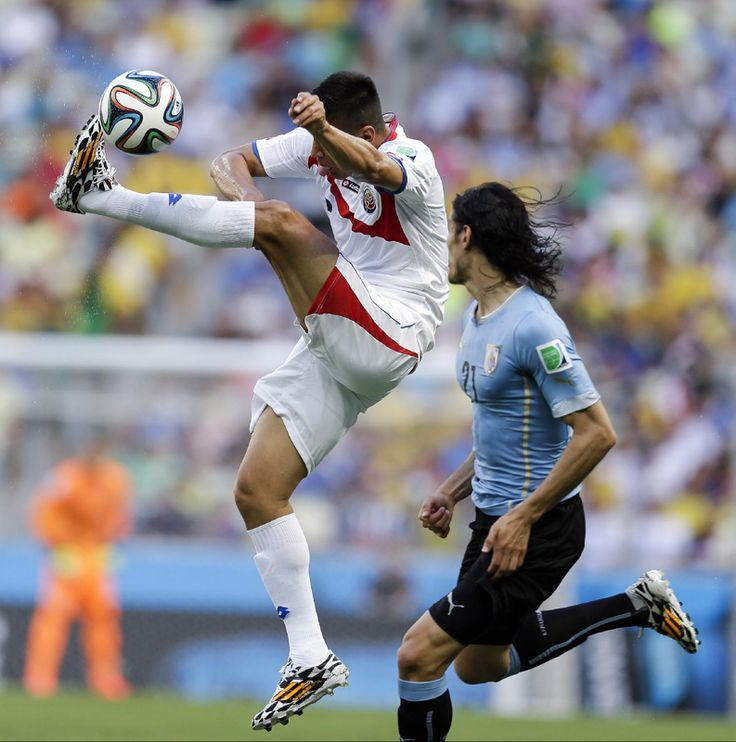 Costa Rica's Oscar Duarte kicks the ball away from Uruguay's Edinson Cavani, right, during the group D World Cup soccer match between Urugua...
