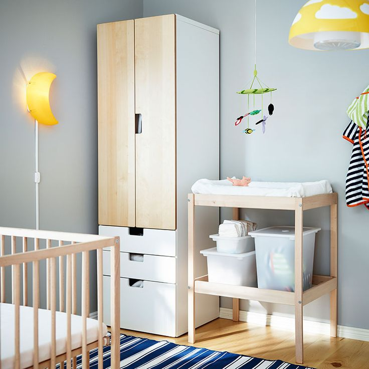 A nursery with changing table and crib in beech and storage in white/birch
