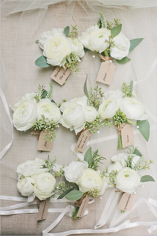 Pinned corsages of white ranunculus with hints of green nagi and leather leaf wrapped in a band of champagne ribbon with the stems showing