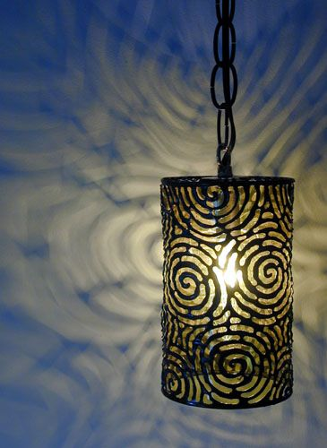 Tin can light fixture with burnt in design.