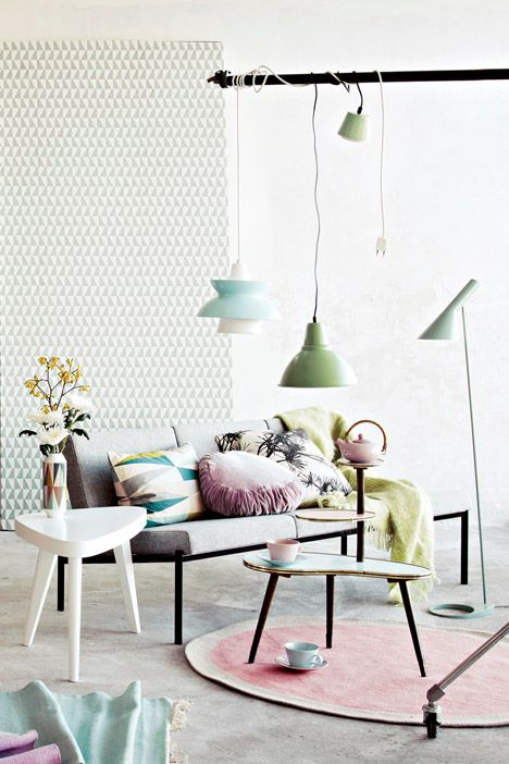 What a serene living room! The pastel colours pop against the white walls and grey sofa.