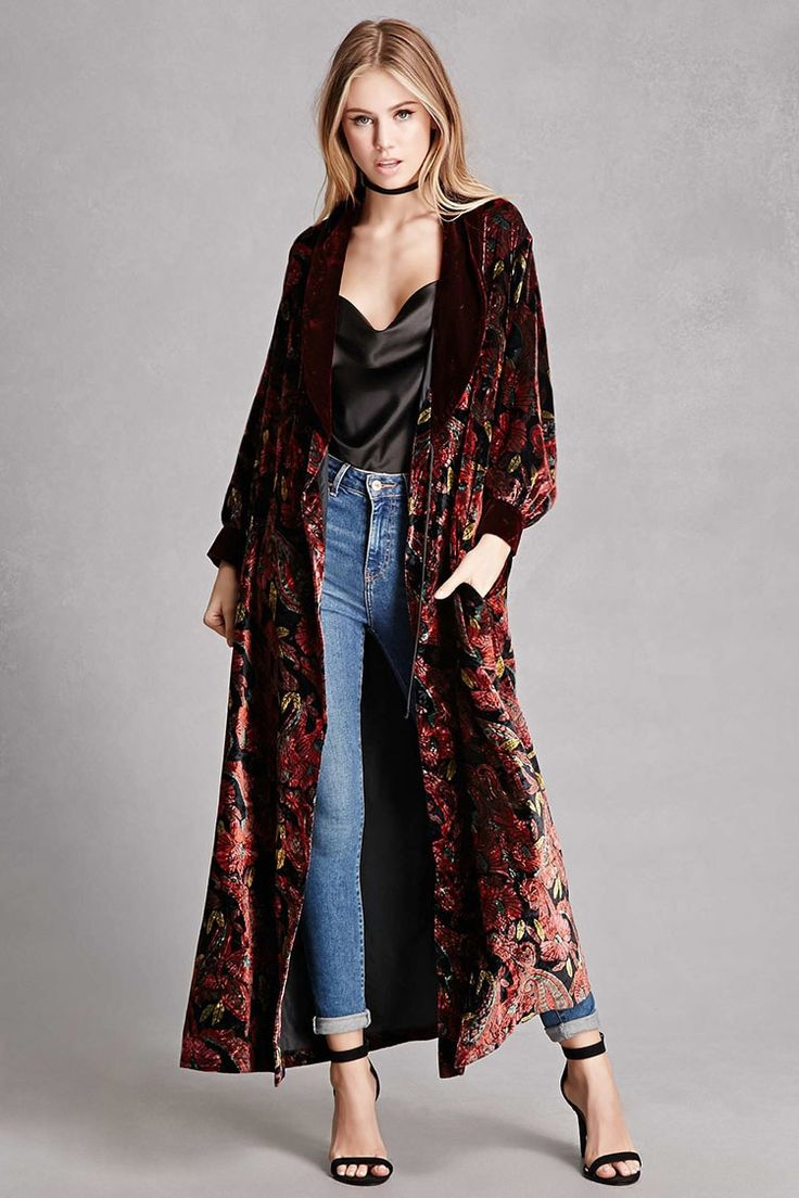 A repurposed vintage velvet kimono featuring an allover floral and paisley print, a contrast shawl collar, long sleeves with cuffs, on-seam pockets, an open front, interior self-tie strings at the waist, and a longline silhouette.